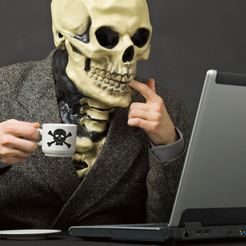 Skeleton drinks poisonous coffee at table with laptop